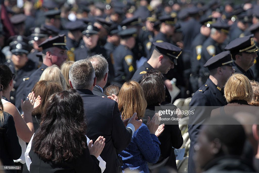 Crowd applauds police exiting following the memorial service for MIT police officer Sean Collier, at Briggs Field, on the MIT campus. Collier was killed during a shootout with the Boston Marathon bombing suspects.