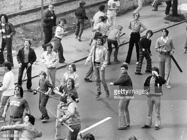 A crowd armed with clubs follows marchers from the Progressive Labor Party who gathered for a march against racism in South Boston on May 3 1975