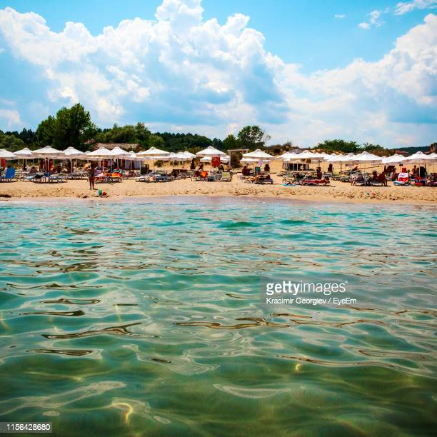crowd at beach against cloudy sky - krasimir georgiev stock photos and pictures