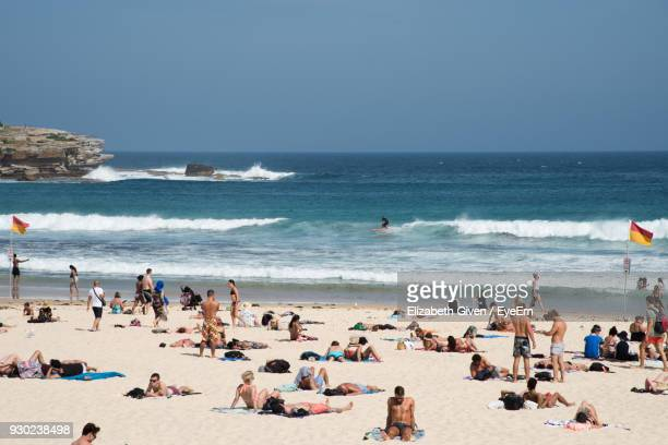crowd at beach against sky - crowded beach stock pictures, royalty-free photos & images