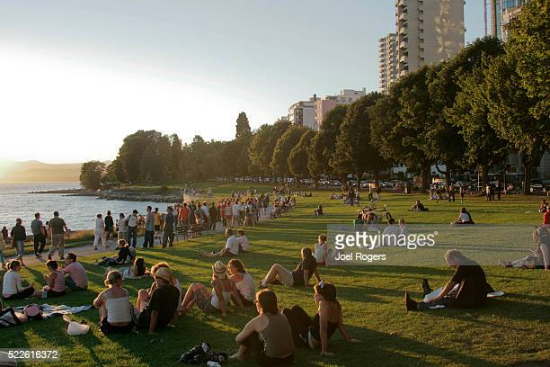 crowd at english bay beach at sunset - english bay stock photos and pictures