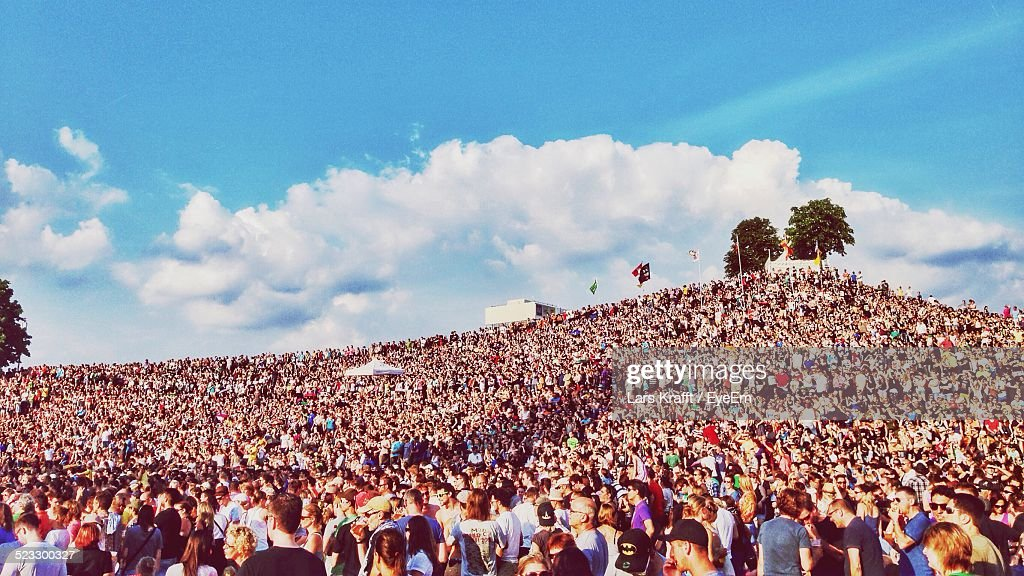 Crowd At Festival On Hill Against Cloudy Sky : Stock Photo