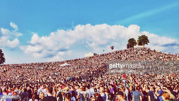 crowd at festival on hill against cloudy sky - music festival stock pictures, royalty-free photos & images