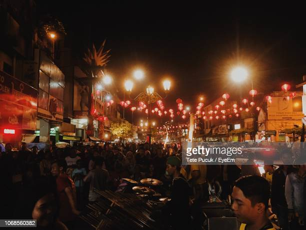 crowd at illuminated city against sky at night - yogyakarta stock pictures, royalty-free photos & images