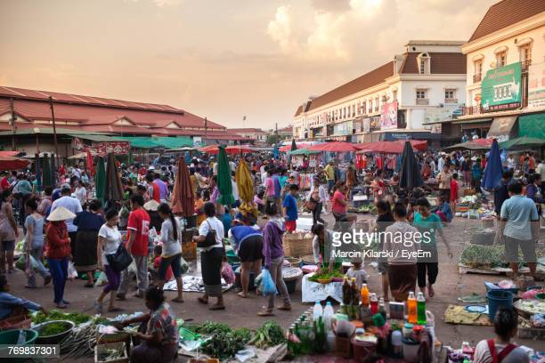 crowd at market in city against sky - laos stock pictures, royalty-free photos & images