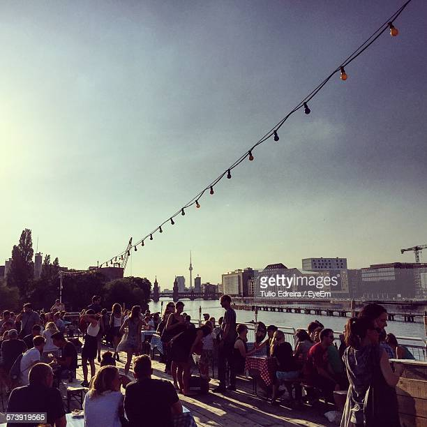 Crowd At Sidewalk Cafe By River In City