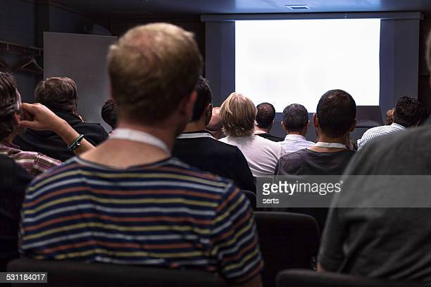 crowd audience looking at blank screen - projection screen stock pictures, royalty-free photos & images