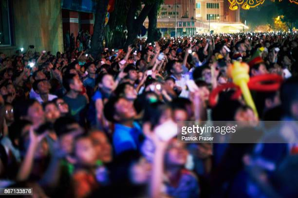 Crowd bathed in multi colored lights takes pictures with smartphones