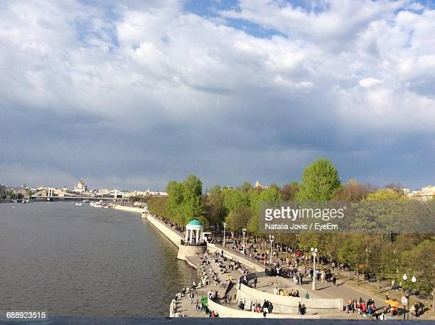 Crowd By River In City Against Cloudy Sky