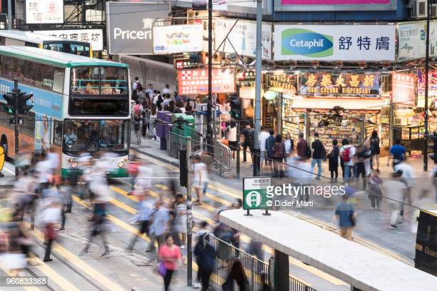 Crowd captured with blurred motion cross the street in the shopping district of Causeway Bay in Hong Kong