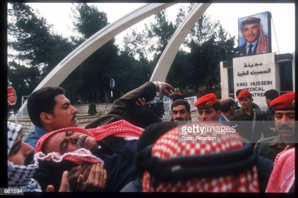 A crowd carries an unconscious man at a vigil February 6 1999 in Amman Jordan King Hussein is in the hospital for treatment of lymphatic cancer