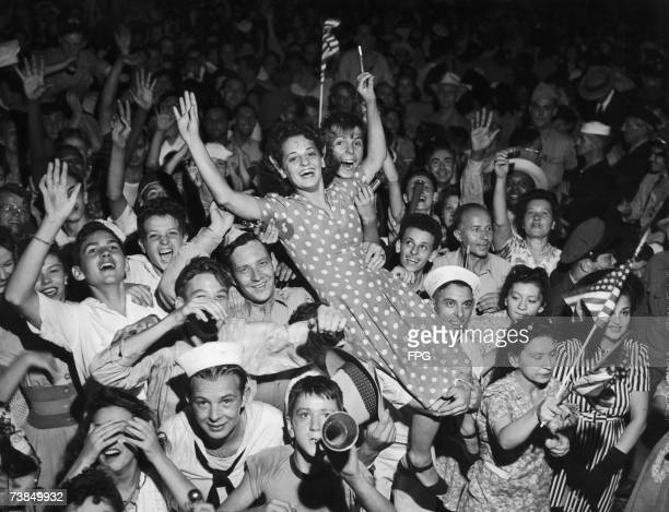 A crowd celebrates the surrender of Japan and the end of the Pacific War New York 14th August 1945 The woman held aloft has 'VJ DAY' written on her...