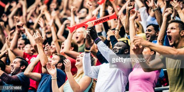 crowd cheering for their team with arms raised - match sportivo foto e immagini stock