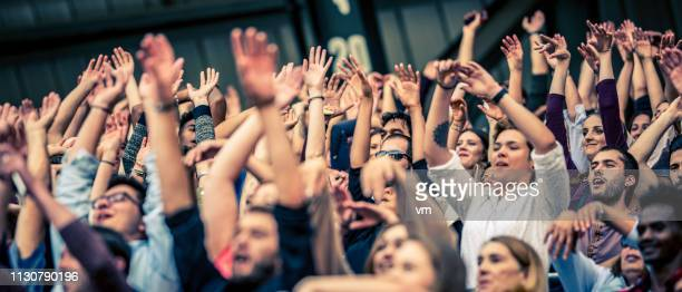 multitud animando a su equipo con los brazos levantados - partido rondas deportivas fotografías e imágenes de stock