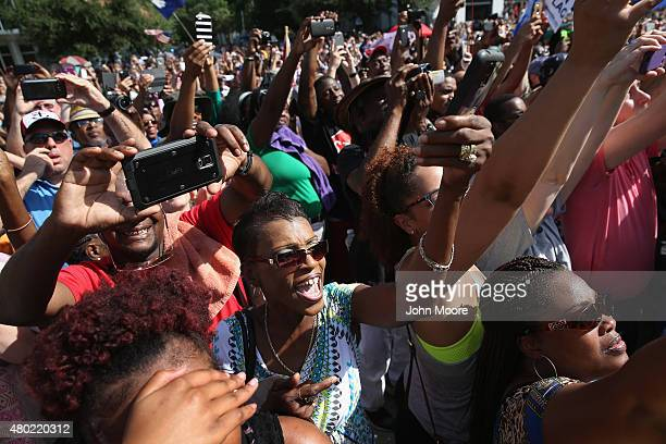 A crowd cheers as a South Carolina honor guard lowers the Confederate flag from the Statehouse grounds on July 10 2015 in Columbia South Carolina...
