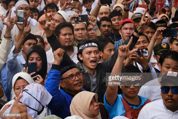 A crowd cheers as an Islamic cleric makes a speech outside the home of Indonesian Presidential Candidate Prabowo Subianto two days after a general...