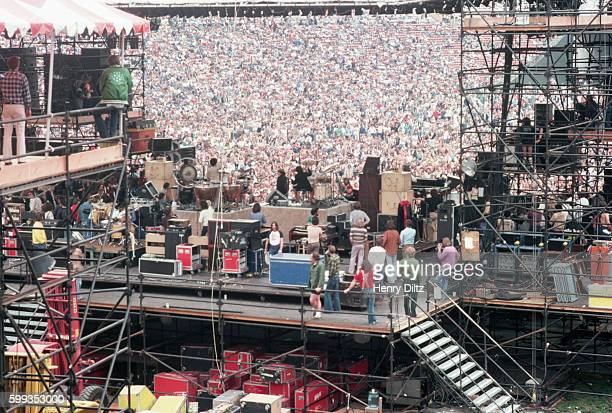 A crowd cheers for a rock band playing on stage in a stadium