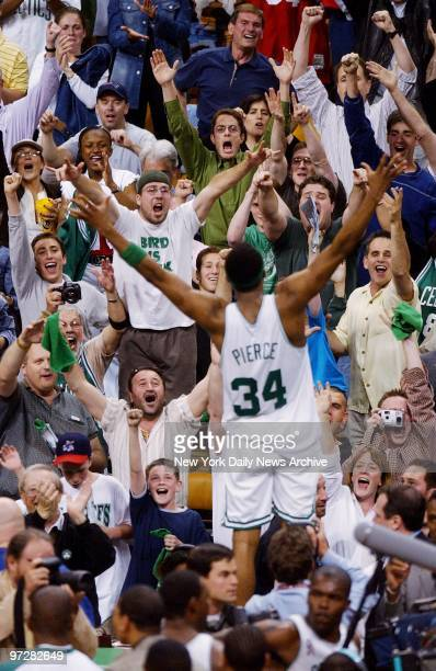 Crowd cheers wildly as Boston Celtics' Paul Pierce leaps up on scorer's table at end of Game 3 of the Eastern Conference finals against the New...
