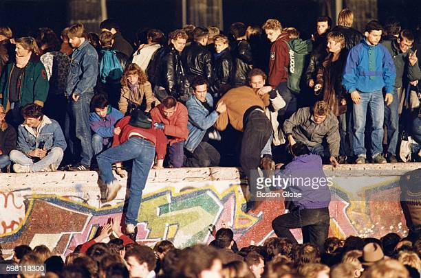 A crowd climbs the Berlin Wall in front of the Brandenburg Gate in West Berlin Germany as the Wall opened up at Checkpoint Charlie on Nov 10 1989