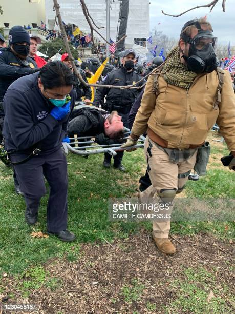 Crowd control barrier is used as a stretcher by police officers transporting a protester outside the US Capitol in Washington DC on January 6, 2021....