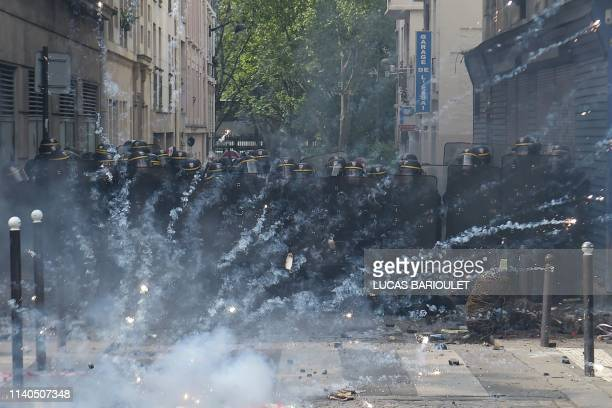 Crowd control canister explodes in front of riot policemen during clashes with protesters on the sidelines of a May Day demonstration in Paris, on...