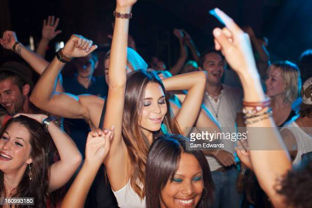 Crowd dancing on dance floor of nightclub