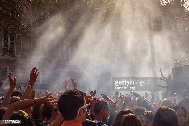 Crowd dancing under the sunny rays of light for the annual Techno Parade festival on september 15th 2012, Paris, France. The techno parade is an...