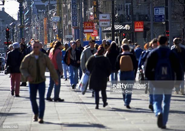 Crowd, dressed warmly, walking on sidewalk in city, blurred.