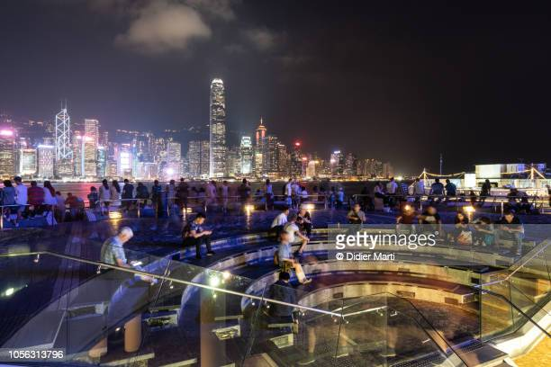 crowd enjoy a night view of hong kong island skyline - hong kong stock pictures, royalty-free photos & images