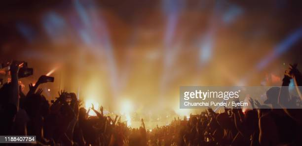 crowd enjoying concert at night - popular music concert stock pictures, royalty-free photos & images