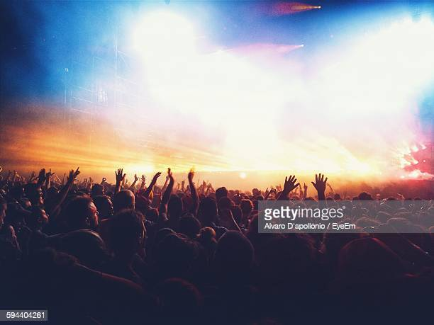 crowd enjoying illuminated music concert at night - concert stock pictures, royalty-free photos & images