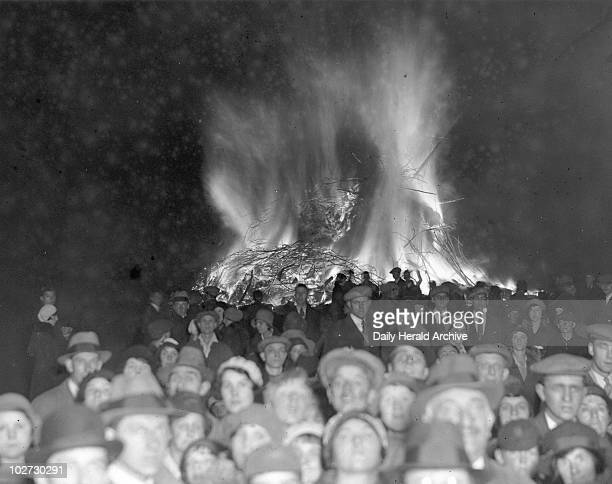 A crowd faces the camera while a bonfire burns in the background Guy Fawkes Night Staines Surrey November 1931 A crowd faces the camera while a...