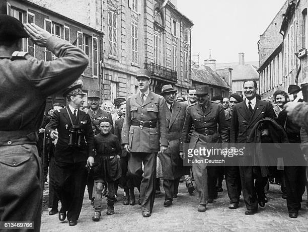 A crowd follows General Charles de Gaulle through the streets of Bayeux during his visit to the French town in 1944