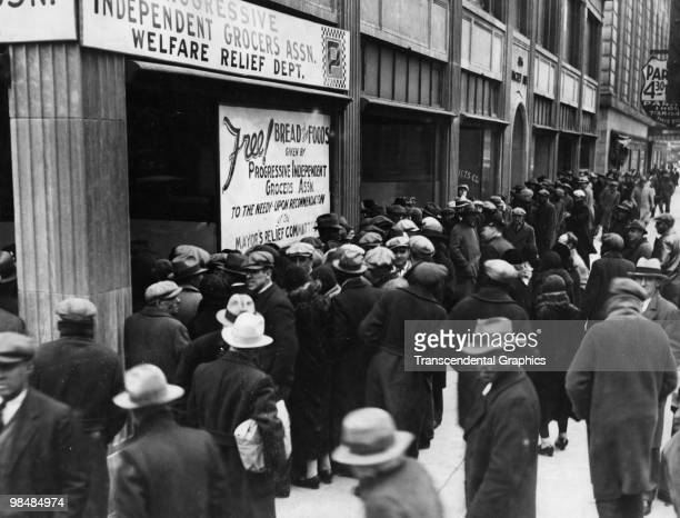 A crowd forms outside the office of the Progressive Independent Grocers Association which gives out bread and food to the needy New York 1932