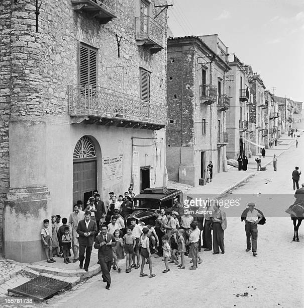 A crowd gather as mafia boss Charles 'Lucky' Luciano leaves a building while in exile in Sicily Italy 31 December 1948