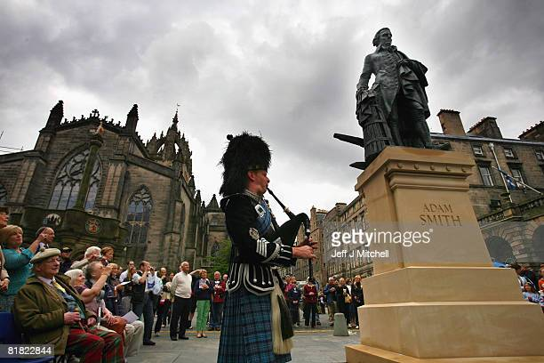 A crowd gather to watch the unveiling of a 10ft bronze statue of Scottish economist philosopher and author Adam Smith at the Royal Mile on July 4...