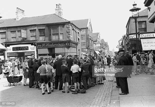A crowd gathered around a group of Salvation Army musicians on a street in Middlesborough 11th August 1945 Original Publication Picture Post 2062...