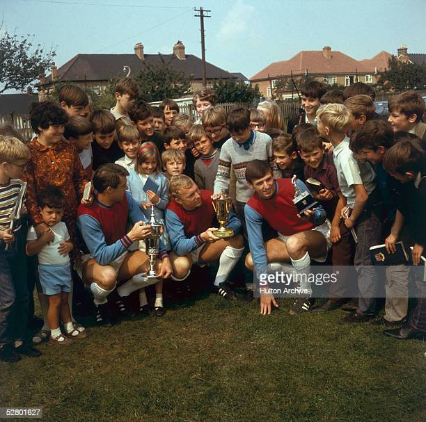 A crowd gathered around the three West Ham footballers left to right Geoff Hurst Bobby Moore and Martin Peters who are each holding a trophy 16th...