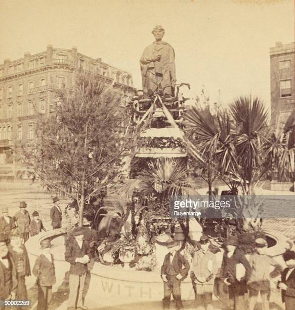 Crowd gathered in front of a statue of Abraham Lincoln in Union Square Park which has been decorated for Memorial Day