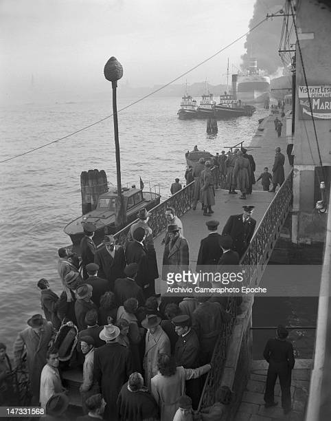 Crowd gathering on a bridge to see the oiler tank Luisa on fire Giudecca Venice 1951