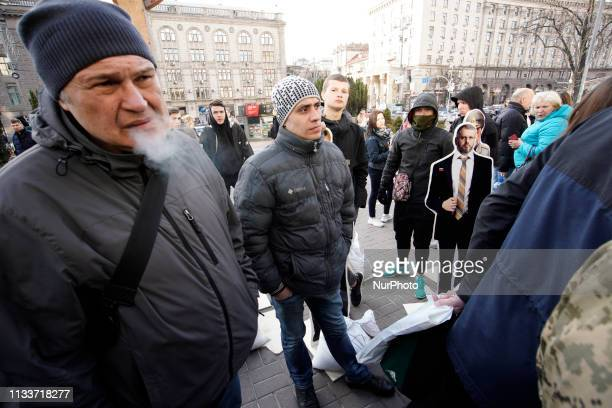 A crowd gathers around an popup exhibit with cutout figures of presidential candidates including a figure of Russian president Vladimir Putin in Kyiv...