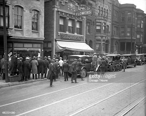A crowd gathers around gangster Dean 'Dion' O'Banion's flower shop Schofield Co at 738 N State Street in Chicago after he was shot seven times with a...