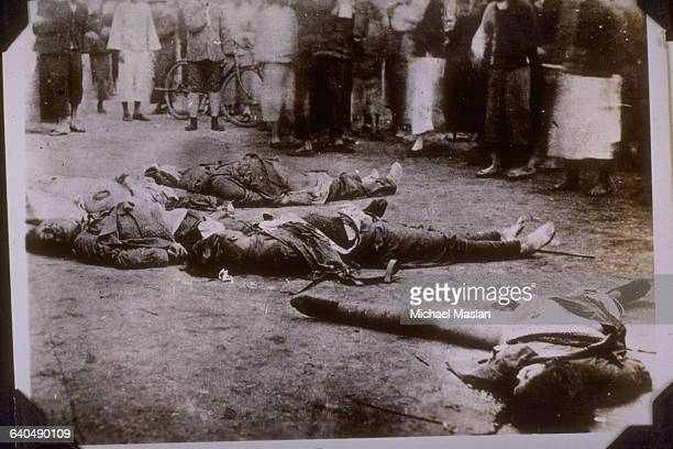 A crowd gathers around the bodies of executed communist girls and the CantonRussian ViceConsul who lies in the center Canton China ca 1928
