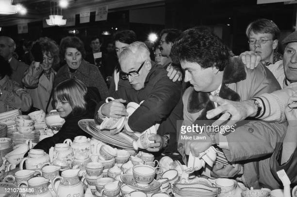 Crowd gathers before a display of crockery on sale, with one man holding plates and cups in his arms, as the arms of other shoppers reach out for a...