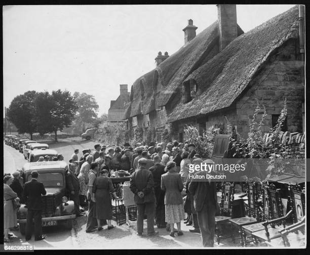 A crowd gathers for the furniture auction outside a cottage