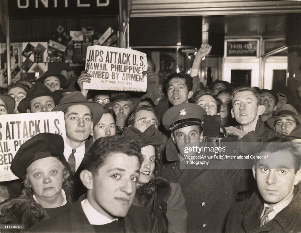 A crowd (with at least one member of the armed forces among them) gathers in Times Square after the Japanese attack on Pearl Harbor, New York, New York, December 8, 1941. Several people hold a copies of the New York Enquirer with the headline 'Japs Attack U.S.; Hawaii, Philippines, Bombed By Airmen!' (Photo by Weegee (Arthur Fellig)/International Center of Photography/Getty Images)