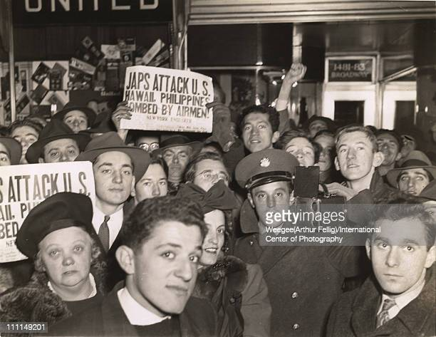 A crowd gathers in Times Square after the Japanese attack on Pearl Harbor New York New York December 8 1941 Several people hold a copies of the New...
