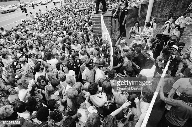 A crowd gathers outside the gates of Graceland for the funeral of Elvis Presley