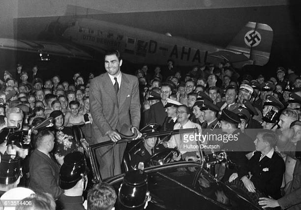 A crowd gathers to greet heavyweight boxer Max Schmeling upon his arrival at the Berlin airport
