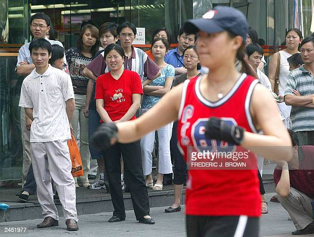 A crowd gathers to watch a fitness display during a promotion for a gymnasium in Beijing 25 June 2003 one day after the World Health Organisation...